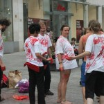 six people, five wearing white t-shirts with red hand prints, one having upper body covered in red hand prints