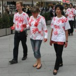 four people wearing white t-shirts with red hand prints walk through the inner city