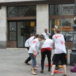 four people wearing white t-shirts with red hand prints, street sign in the back says stephansplatz