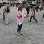 one person wearing white t-shirt with red hand prints hands out flyers