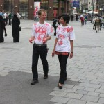 two people wearing white t-shirts with red hand prints