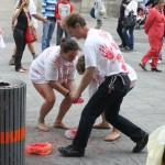 three people wearing white t-shirts with red hand prints removing paint from the street