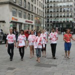 flash mob walks through inner city while one of them hands out flyers