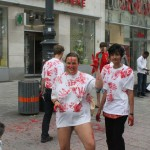four people wearing white t-shirts with red hand prints