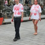 two people wearing white t-shirts with red hand prints walking through inner city
