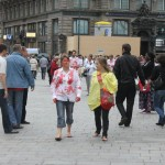 people wearing white t-shirts with red hand prints talking to bystanders