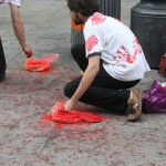 two people cleaning the street which is covered in red paint