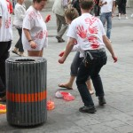 four people wearing white t-shirts with red hand prints, one of them looks like he is dancing