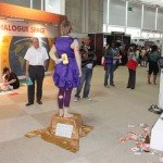 a living statue seen from behind, the person is standing still with one arm behind her back, holding a hammer shaped toy, a sign at her feet says: why are we doing this? get informed at booth nr.: 644, a bloody hands action